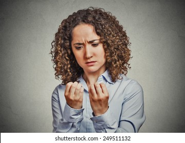 Closeup portrait worried woman looking at hands fingers nails obsessing about cleanliness isolated grey wall background. Negative human emotion facial expression feeling body language perception