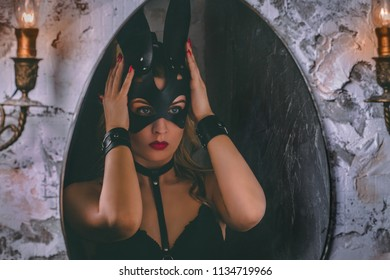 Close-up portrait of a young adult girl dressing a leather rabbit mask in front of mirror.