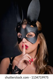 Close-up portrait of a young adult girl in a leather rabbit mask looks at camera, covers her mouth with a finger. Black wall background.