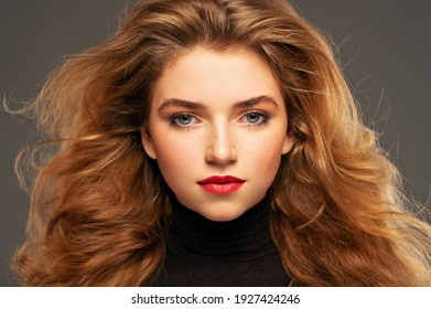 Closeup portrait of an young adult girl with long curly hair.  Photo of a fashion model posing at studio. Pretty young woman with red lips looking at camera. Beauty portrait.
