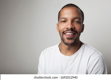 Close-up portrait of young African American young black man wearing T-shirt against white wall with happy face.