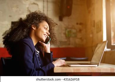 Closeup portrait of young african woman relaxing in cafe with laptop and making phone call