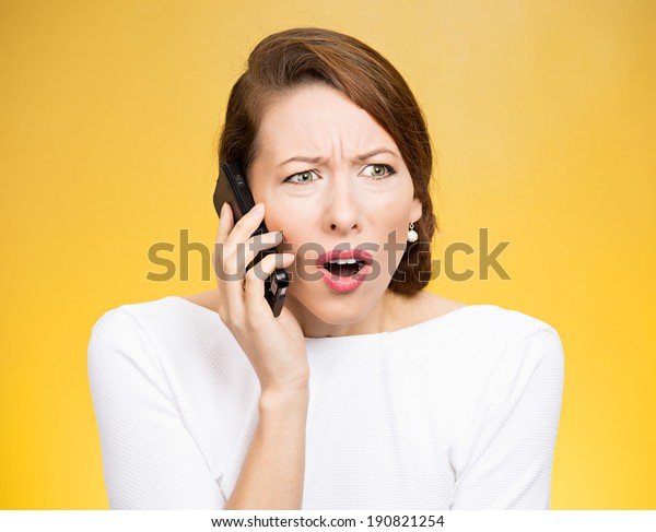 Closeup portrait young angry business woman, corporate employee talking on cell phone, having unpleasant, bad conversation, isolated yellow background. Negative emotions, facial expressions, reaction