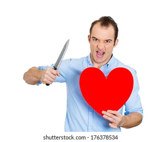 Closeup portrait of young angry man, desperate mad guy, looking crazy, screaming, holding heart and knife in hands, isolated on white background. Relationship, divorce, separation, broken love concept