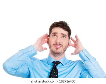 Closeup portrait young angry, unhappy, stressed business man covering ears, looking up, thinking stop making loud noise giving me headache, isolated white background. Negative emotion, face expression