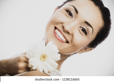 Close-up portrait of young asian woman holding white gerber flower isolated on white background.