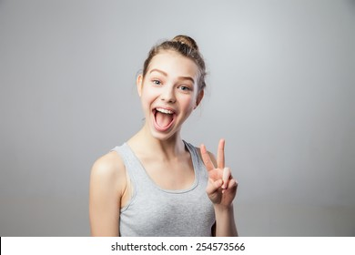 Closeup portrait young attractive blonde woman, student, beautiful girl with v fingers move, isolated grey background. Positive human emotions, face expressions, attitude