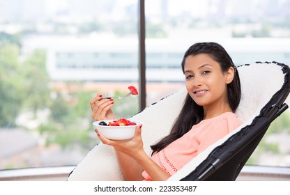Closeup portrait of a young, attractive businesswoman, eating fruits, berries, nutrition and diet concept, healthy living,  urban lifestyle, Isolated glass window indoor greenery background.