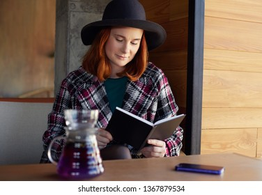 Closeup portrait of young attractive European redheaded freckled woman in hat and coat, sitting in trendy urban cafe, reading notes in scratchpad, drinking tea during coffee break in her office job