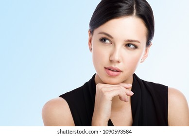 Close-up portrait of a young attractive woman looking away. To think about something or to choose. Isolated on blue background with empty space