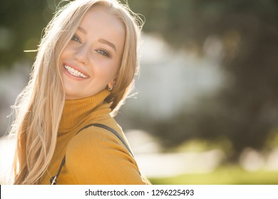 Closeup portrait of young attractive woman outdoors with copy space. Beautiful blond girl model. Cheerful lady on neutral background spring, fall, autumn.
