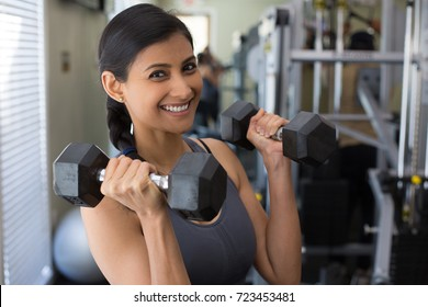 Closeup portrait, young attractive woman lifting weight in gym, indoors with equipment in the background