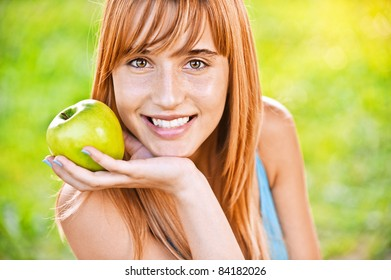 Close-up portrait of young attractive woman holding an apple, propping up her face and smiling at summer green park.