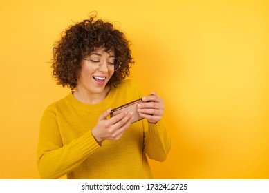 Close-up portrait of young beautiful Arab businesswoman holding in hands cell playing video games or chatting isolated on bright vivid shine yellow background