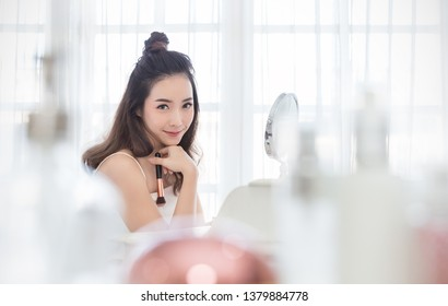 Closeup portrait of young beautiful asian girl using brush with mirror for makeup routine. Beauty woman with perfect glow skin dress up. Health care woman asia lifestyle cosmetic blogger concept