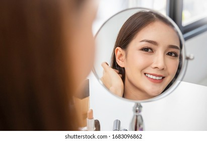 Closeup portrait of young beautiful asian girl with mirror makeup routine with copy space. Beauty influencer woman with perfect glow skin dress up. Healthcare woman lifestyle cosmetic blogger concept