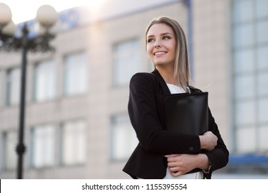 Close-up portrait of young beautiful blonde girl outdoor next to building in jacket and with notepad. Business, work and education.