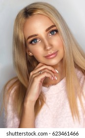 Close-up portrait of young beautiful blonde girl with nude male-up and long hair.