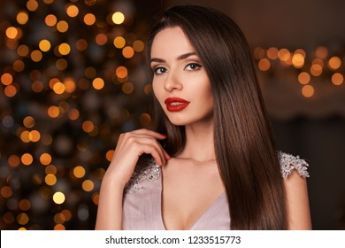 Closeup portrait of young beautiful brunette woman with straight hair, makeup and red lips. Pretty girl in evening dress posing against christmas lights bokeh.