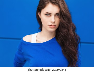 Closeup portrait of young beautiful brunette woman with blue background