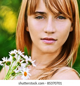 Close-up portrait of young beautiful fair-haired woman with bouquet of camomiles at summer green park.