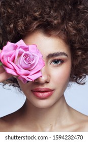 Close-up portrait of young beautiful girl with curly hair, clean makeup and pink rose in her hand