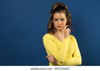 closeup portrait of a young and beautiful girl in yellow spring sweater , posing on blue background. she looks at the camera. commercial shot.