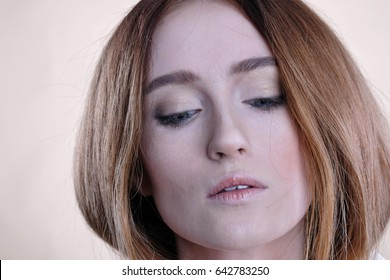 Close-up portrait of young beautiful girl with grey eyes and pale skin. Red-haired woman looking down.  Isolated shot. Skin texture.