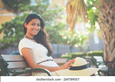 Closeup portrait young beautiful happy woman in white dress, sitting on bench, isolated green palm trees, nature background. Positive human emotion facial expression feelings. Retro faded vintage look