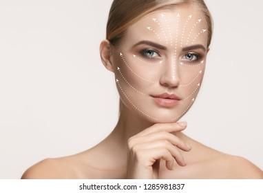 صورة عن قرب لامرأة شابة وجميلة وصحية مع الأسهم على وجهها.  مفهوم السبا والجراحة وشد الوجه والعناية بالبشرة