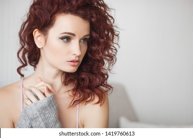 Closeup portrait of young beautiful redhaired woman. Redhead female indoors. Beauty portrait of attractive lady at home with free space.