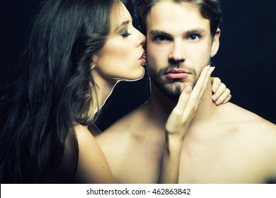 Closeup portrait of young beautiful sexual couple of brunette woman with long hair embracing and kissing handsome muscular man in studio on black background, horizontal picture