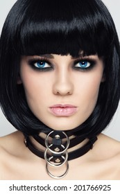 Close-up portrait of young beautiful sexy brunette in black leather collar