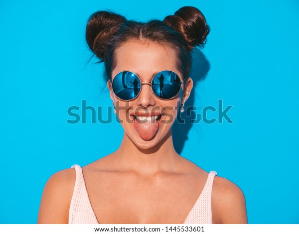 Closeup portrait of young beautiful sexy smiling hipster woman in sunglasses.Trendy positive girl going crazy.Model isolated on blue wall.Shows her tongue
