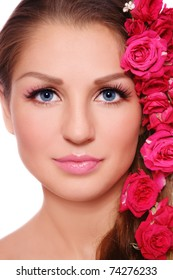 Close-up portrait of young beautiful smiling woman with roses in hair