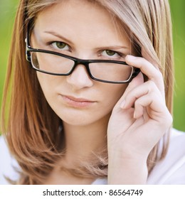 Close-up portrait of young beautiful strict blonde woman looking above her eyeglasses at summer green park.