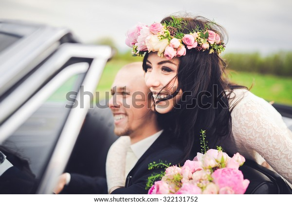 close-up portrait young beautiful stylish couple bride in a white dress with a bouquet of flowers in her hair and and groom in retro car on the way to their honeymoon