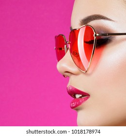 Closeup portrait of young beautiful woman red wearing heart shaped sunglasses. Smokey eyes and red lips. Valentines day, love or makeup concept. Studio shot.