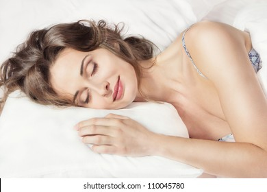 Closeup portrait of a young beautiful woman sleeping on the bed. Sweet dreams. Good night