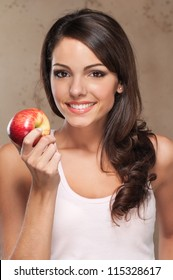 Close-up portrait of young beautiful woman holding an apple