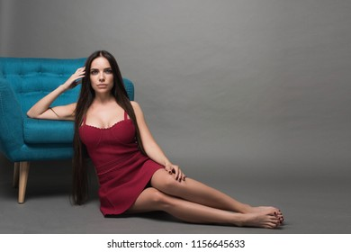 Closeup portrait of young beautiful woman with with beautiful long hair. Sitting and posing in studio. Portrait of trendy, cheerful, modern, stylish, woman in eyewear isolated on grey background.