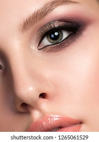 Closeup portrait of young beautiful woman with evening make up. Pink and gold multicolored smokey eyes. Luxury skincare and modern fashion makeup concept. Studio shot.