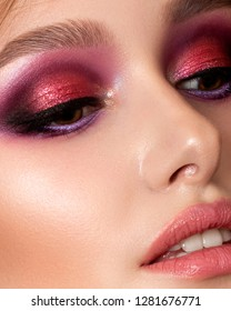 Closeup portrait of young beautiful woman with bright pink smokey eyes and lips. Fashion makeup. Studio shot. Modern summer make up. Extreme closeup, partial face view