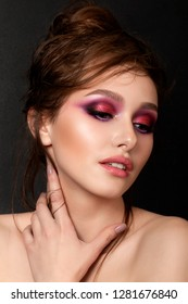 Closeup portrait of young beautiful woman with bright pink smokey eyes. Girl touching her neck. Fashion makeup. Studio shot. Modern bright summer make up