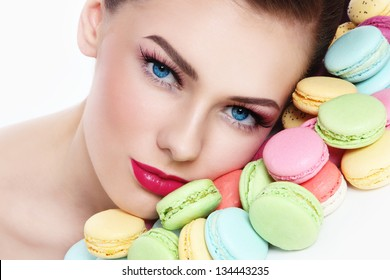 Close-up portrait of young beautiful woman with colorful macaroons