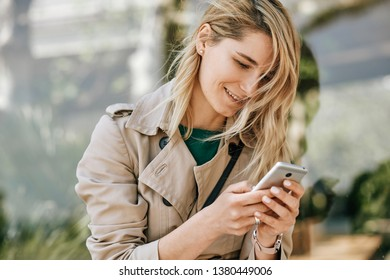 Closeup portrait of young beautiful woman smiling and writing messages on smartphone, sitting outdoor in the city at sunny day. Pretty female reading news on cellphone. Travel and technology concept