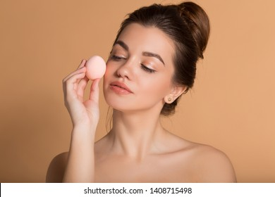 Closeup portrait of young beautiful woman is holding beauty blender for applying makeup foundation . Skin care and beauty concept.