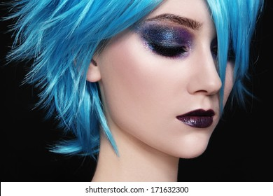 Close-up portrait of young beautiful woman in blue cosplay wig