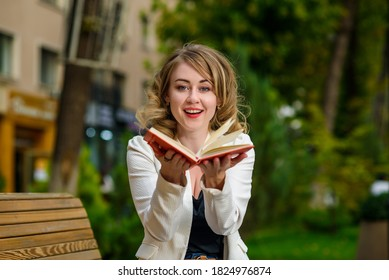 Closeup portrait of young beautiful woman with book in hands