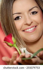 Close-up portrait of young beautiful woman with red rose